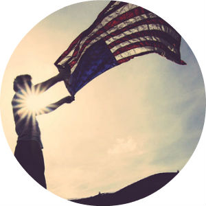 Man Waving an American Flag with Sun Behind Him