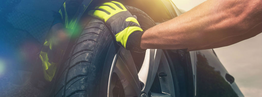 A Mechanic's Hands with Gloves Putting on a New Tire