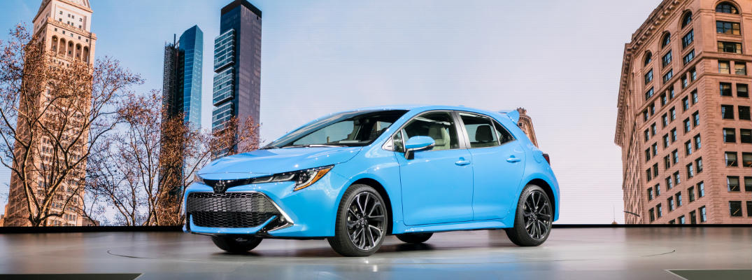 Blue 2019 Toyota Corolla Hatchback XSE on Stage at an Auto Show with City Skyline Backdrop