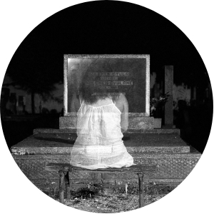 black and white picture of a female ghost sitting at a headstone