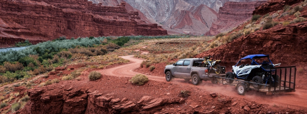 Gray 2019 Toyota Tacoma on a Desert Trail Towing a Trailer with ATV