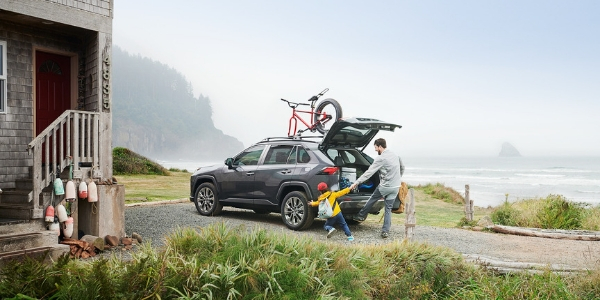 Dad and Child Loading Cargo in Gray 2019 Toyota RAV4