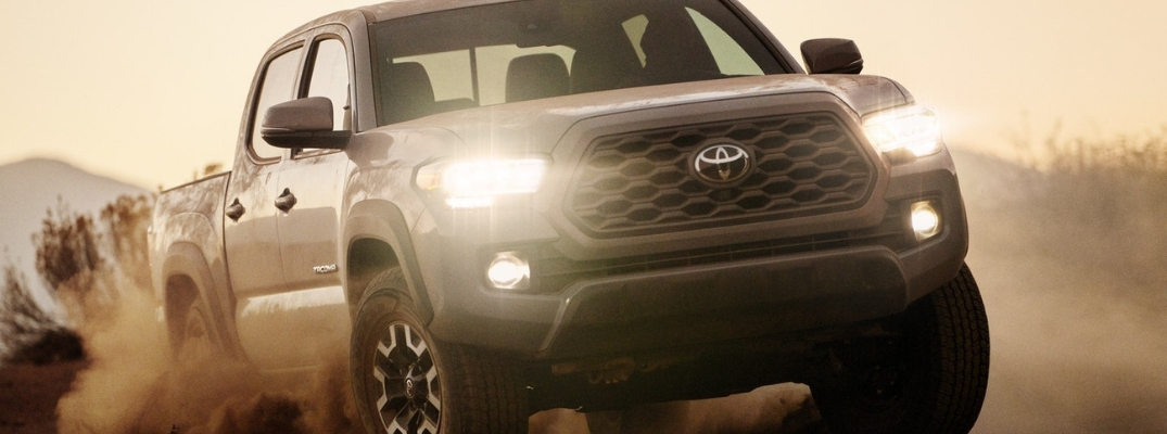 Gray 2020 Toyota Tacoma Kicking Up Dust on a Trail with Headlights On