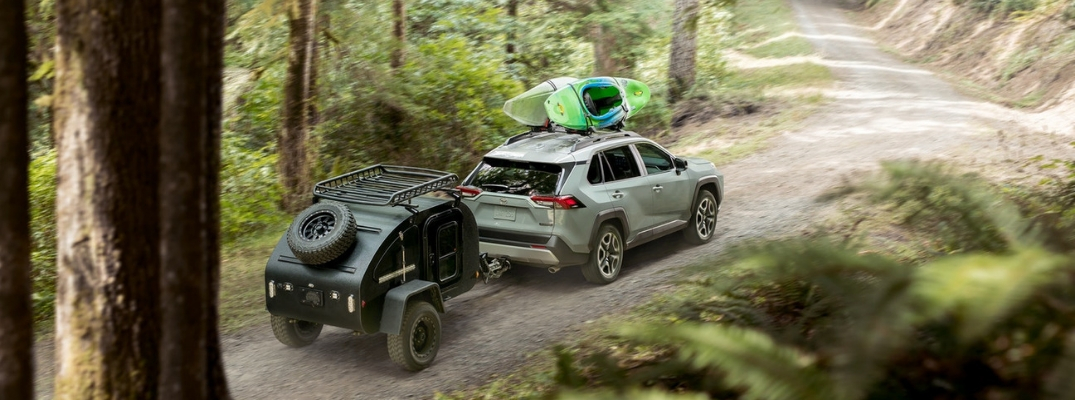 Gray 2019 Toyota RAV4 Towing a Small Trailer with Kayaks on the Roof on a Dirt Road