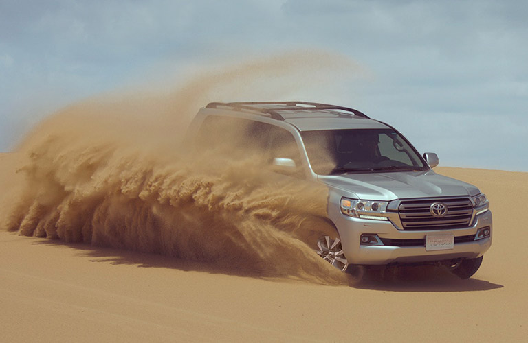 Silver 2019 Toyota Land Cruiser Kicking Up Sand in the Desert