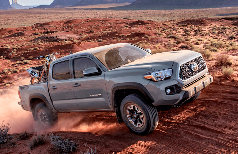 Gray 2019 Toyota Tacoma on Desert Trail with Dirt Bike in the Bed
