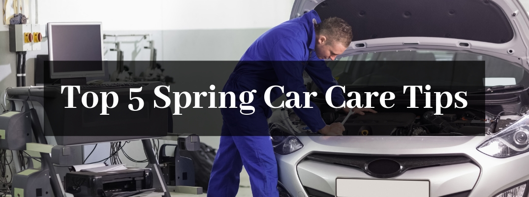 Mechanic in Blue Working Under the Hood of a Silver Car with Black Rectangle and White Top 5 Spring Car Care Tips Text
