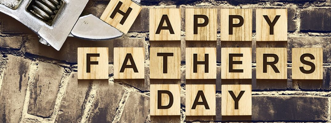 Wood Blocks Spell Out Happy Father's Day on Brick Background