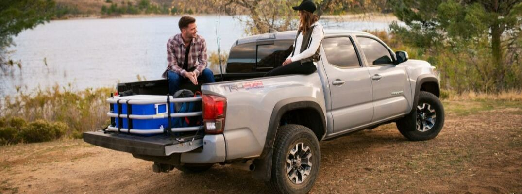 Man and Woman Sitting in the Bed of a Gray 2019 Toyota Tacoma with Bed Extender and Cooler