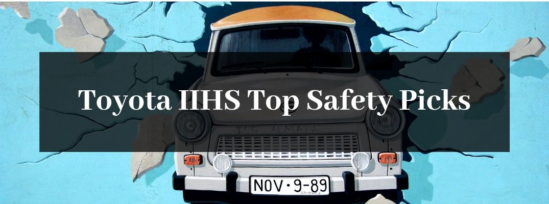 White Model Car Breaking Through a Blue Wall with Black Text Box and White Toyota IIHS Top Safety Picks Text
