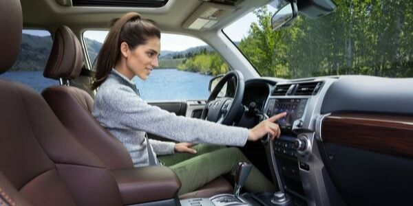 Woman in the Front Seat of 2020 Toyota 4Runner Using Touchscreen