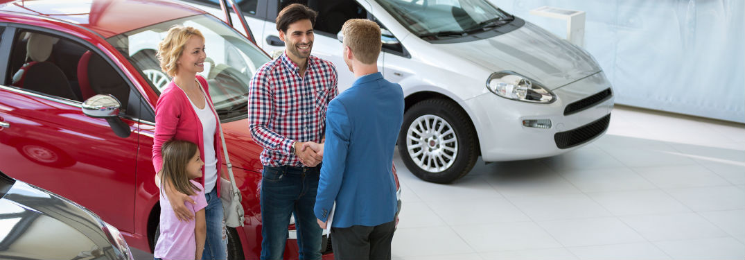 family shaking hands with salesman'