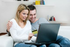 A man and woman sitting in front of a computer