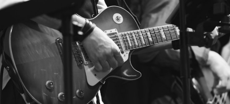 black and white electric guitar being played