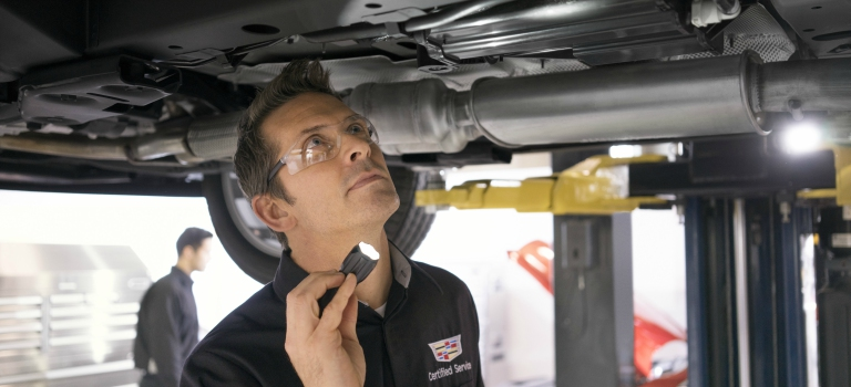 Man looking at the undercarriage of a Cadillac in a shop