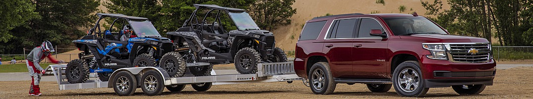 2018 Chevy Tahoe red side view towing some ATVs