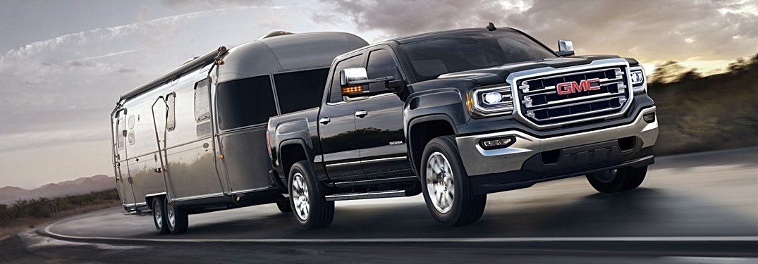 2018 GMC Sierra 1500 black towing a silver trailer side view