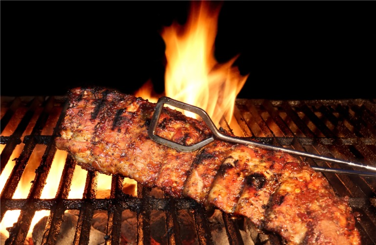 BBQ ribs on a grill being flipped with flames