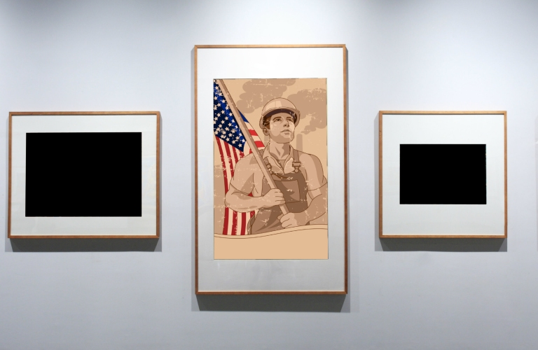 labor picture in a frame next to two blank paintings