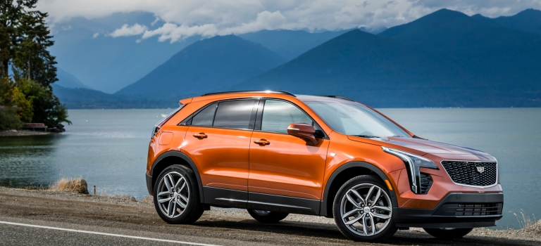 2019 Cadillac XT4 orange side view in front of water