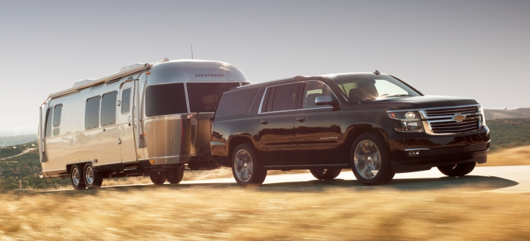 2019 Chevy Suburban towing a trailer black side view