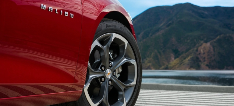 2019 Chevy Malibu red close up of rim looking over a lake and mountain