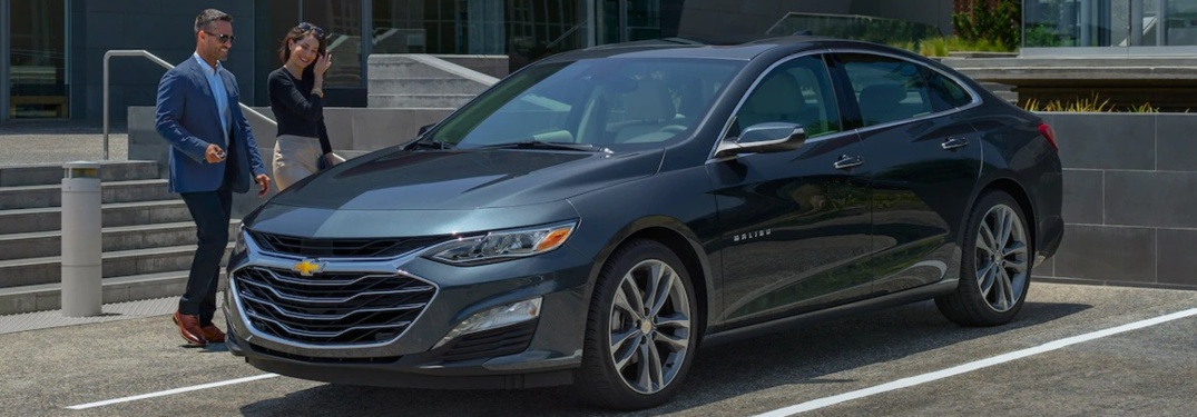 2019 Chevy Malibu silver side view with couple walking toward it