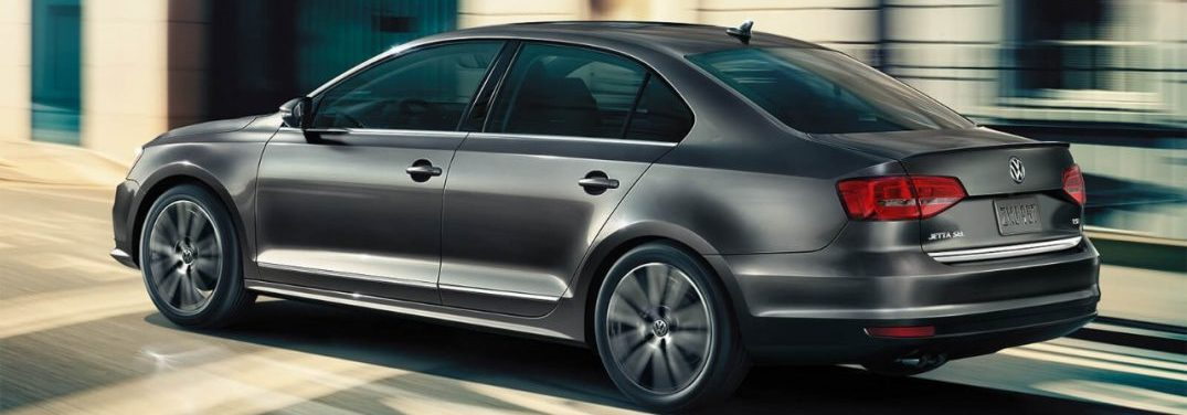 2018 Volkswagen Jetta driving down a street with a blurry background