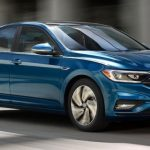 2019 Volkswagen Jetta side profile driving on a highway by some pillars