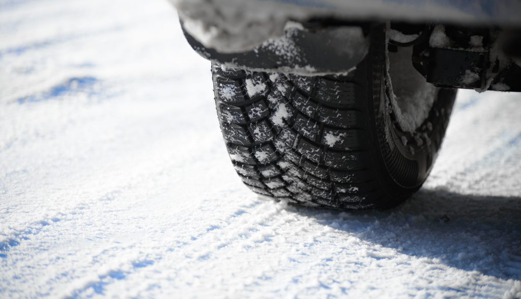 Close-up Image of Winter Car Tire on the Snowy Road
