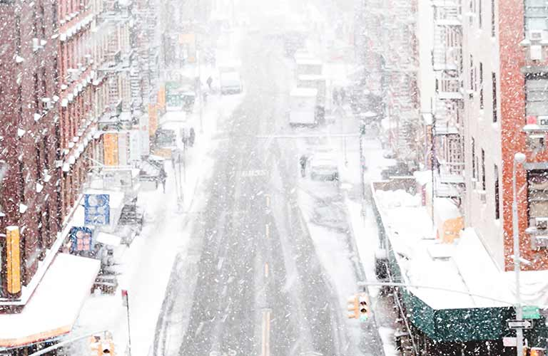 A snowy city street with cars parked along the sides of the road and tall brick buildings.