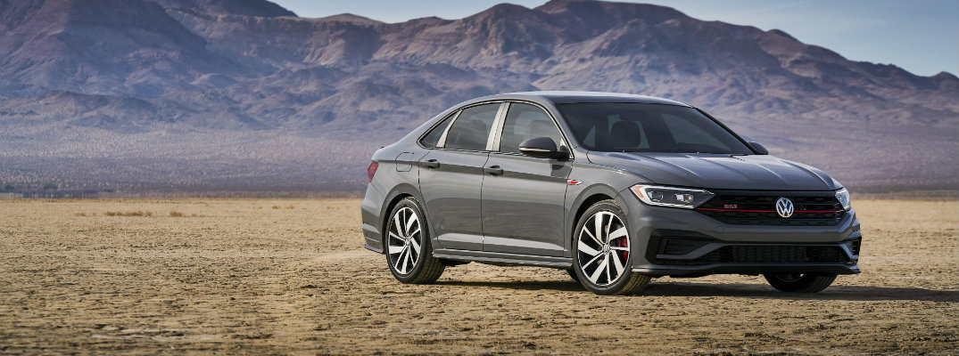 2019 Volkswagen Jetta GLI exterior shot with dark gray metallic paint color parked in a desert with a mountain range far behind it