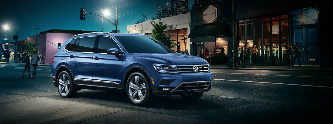 2019 Volkswagen Tiguan exterior shot with blue color paint job parked at the side of a street at night under a lamp post as people cross the street