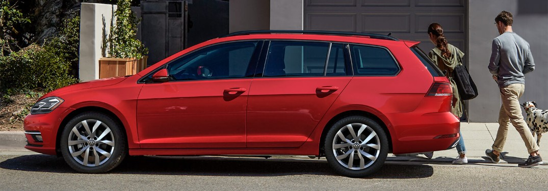 Driver side of a red 2019 Volkswagen Golf SportWagen parked in front of a home with a couple and their Dalmatian walking to the home