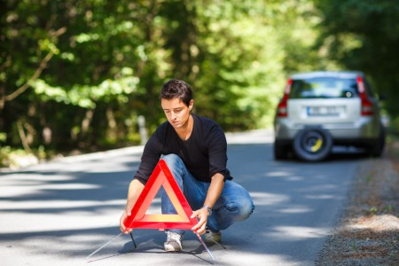 Man placing a reflective triangle on the road behind his vehicle