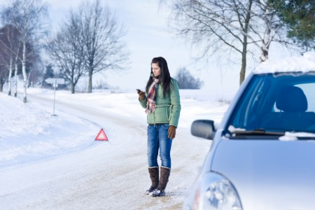 Woman dialing a number to call for help in the winter with a triangle behind her and her vehicle to her left