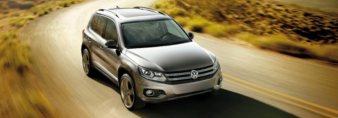 Silver 2017 Volkswagen Tiguan drives down a country road.