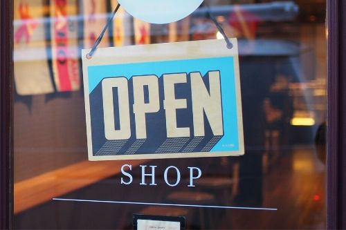 """A sign on the door of a store says """"open."""" Beneath it is written, """"shop."""""""