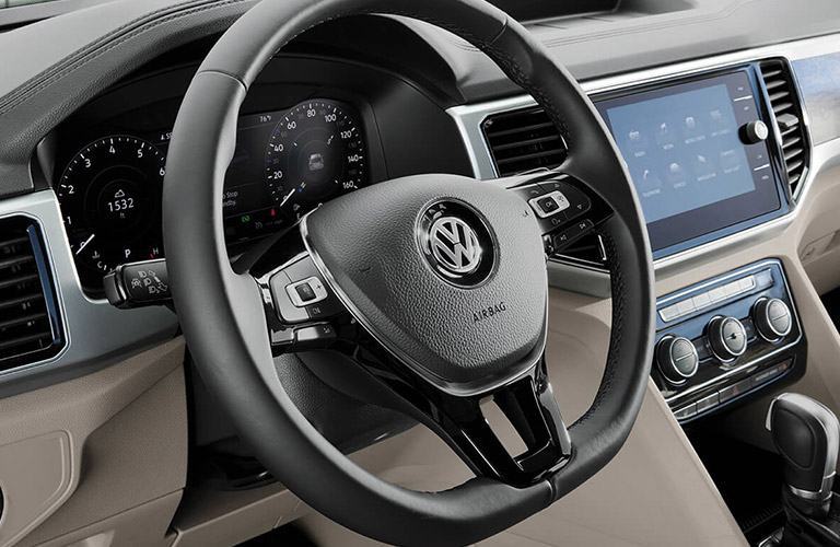Interior front steering wheel and infotainment screen inside a 2019 Volkswagen Atlas.