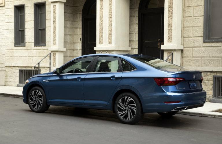 Blue 2019 Volkswagen Jetta parked outside a building. Rear/side view.