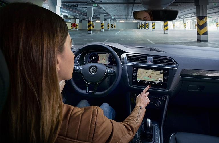 Woman fiddles with the navigation screen inside a 2020 Volkswagen Tiguan