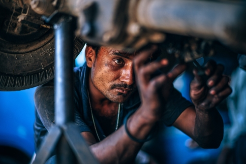 Mechanic works intently on the underside of a vehicle.