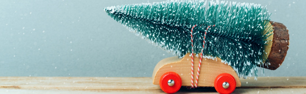 A toy car rolls along with a large Christmas tree tied to its back.
