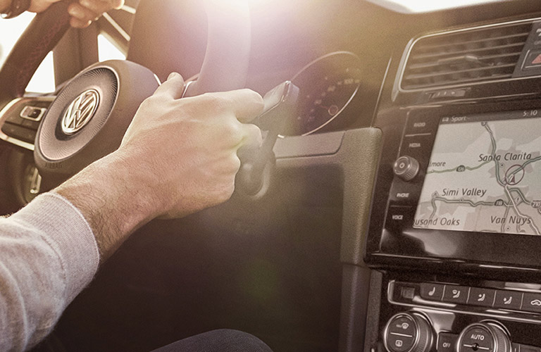 Hands grip the wheel by the navigation system inside a 2020 Volkswagen Golf GTI.