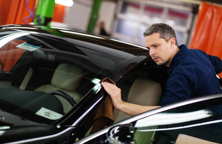 A mechanic polishes the windshield of a car.