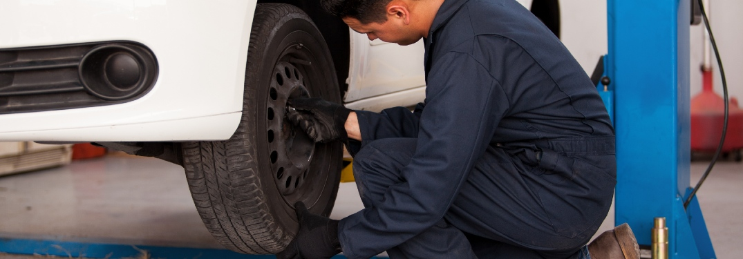 A man performs a tire rotation on a white vehicle in a shop.