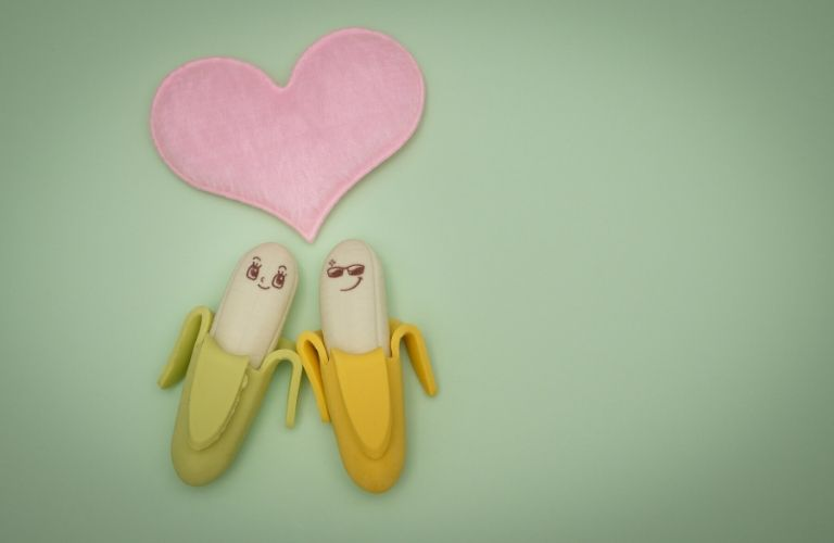 Two bananas gaze at each other lovingly as a heart floats above their heads.