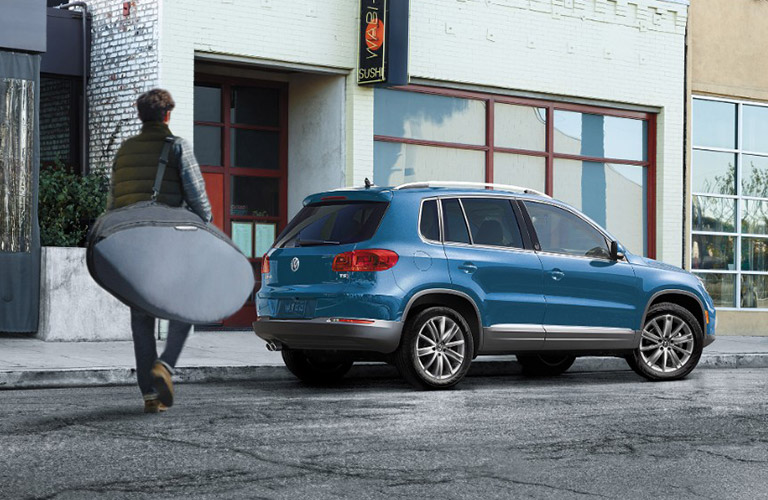 Man with a large bag approaches a blue 2017 Volkswagen Tiguan.