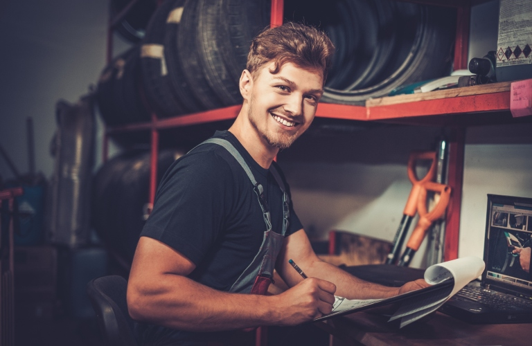 A mechanic smiles and fills out a form.