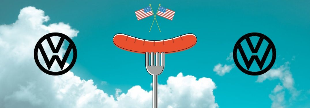 A sausage skewered on a fork, flanked by the VW logo and topped by two American flags on the background of a blue sky with white clouds drifting in.